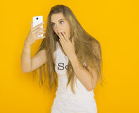 Unhappy young attractive woman very surprised something on her smartphone. Unhappy young attractive woman with tousled hair very surprised something on her Royalty Free Stock Photography