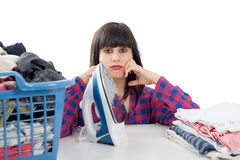 Unhappy young beautiful woman ironing clothes. An unhappy young beautiful woman ironing clothes Stock Photography