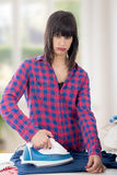 Unhappy young beautiful woman ironing clothes. An unhappy young beautiful woman ironing clothes Stock Images