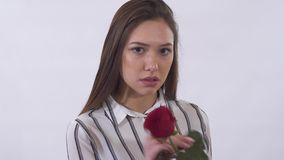Unhappy young beautiful woman is very sad pulling up petals from the red rose. Shooting in the studio on a white. Unhappy young beautiful woman is very sad stock video footage