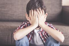 Desperate child hidding his face Stock Image