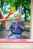 Unhappy Young boy playing in the sandbox Royalty Free Stock Photos
