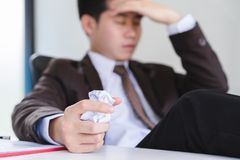 Unhappy young businessman hand holding a crumpled paper and another squeezing head stock image