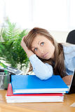 Unhappy young businesswoman sitting at her desk Stock Photos