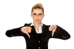 Unhappy young businesswoman with thumbs up Stock Photography