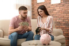 Unhappy young couple with money at home. royalty free stock photo
