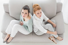 Unhappy young female friends not talking after argument on the couch Stock Photography