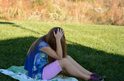 Unhappy young girl. Unhappy young girl sitting alone on the grass Royalty Free Stock Photography