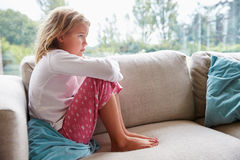 Unhappy Young Girl Sitting On Sofa At Home Stock Photos