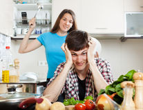 Unhappy young man with angry wife at home Stock Images