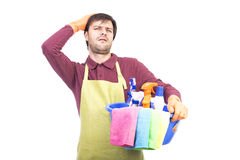 Unhappy young man with apron and cleaning equipment. Over white bachground Stock Photo
