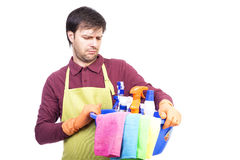 Unhappy young man with apron and cleaning equipment Royalty Free Stock Image