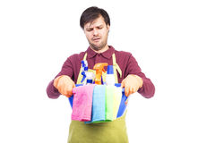 Unhappy young man with apron and cleaning equipment Royalty Free Stock Images