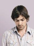 Unhappy Young Man Looking Down. Closeup of unhappy young man looking down isolated on colored background Stock Photos