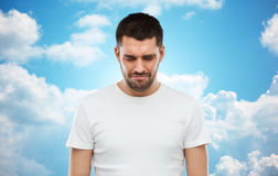 Unhappy young man over blue sky background Royalty Free Stock Image