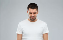 Unhappy young man over gray background Royalty Free Stock Photo