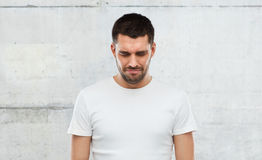 Unhappy young man over gray wall background Royalty Free Stock Image