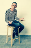 Unhappy young man talking with hands sitting alone on stool Stock Photography