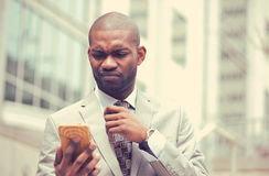 Unhappy young man talking texting on cellphone outdoors. Closeup unhappy young man talking texting on cellphone outdoors. Negative human face expression Royalty Free Stock Image