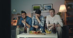 Unhappy young men with sad faces crying watching tv at night in apartment stock video footage