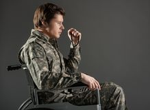 Upset handicapped man wearing military uniform stock images