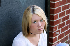 Unhappy Young Woman. Unhappy young blond woman, sitting near an exterior doorway of a building Stock Photography