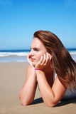 Unhappy young woman. An attractive young woman model brooding in the sand of a beach in front of the blue sea in summer outdoors Stock Photography