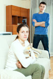 Unhappy young woman against standing man Stock Photos