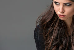Unhappy young woman. Beautiful  unhappy young woman on gray background Stock Photos