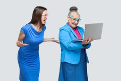 Unhappy young woman shout at happiness older woman work computer Royalty Free Stock Photo