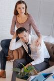 Unhappy young woman comforting her depressed unemployed husband. Support. Sad young beautiful women sitting with her depressed unemployed husband and comforting Stock Photography