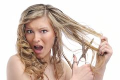 Unhappy young woman cutting hair Stock Photo