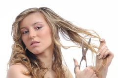 Unhappy young woman cutting hair Stock Photography