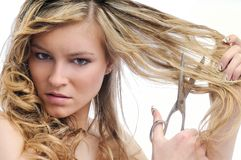 Unhappy young woman cutting hair with scissors Royalty Free Stock Photo