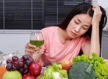 Unhappy woman drinking vegetable juice in kitchen stock photo