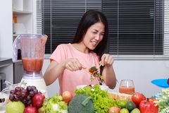 Unhappy woman eating salad in kitchen royalty free stock image