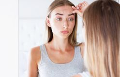 Unhappy young woman in front of a mirror looking at her wrinkles royalty free stock image