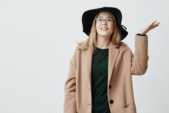 Unhappy young woman frowns face in displeasure, shrugs shoulders, has bad mood, being upset because of rainy weather. Checks weather it continues raining Royalty Free Stock Photography