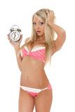 Unhappy woman with an alarm clock. Royalty Free Stock Image