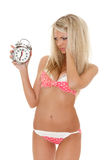 Unhappy woman with an alarm clock. Royalty Free Stock Photos