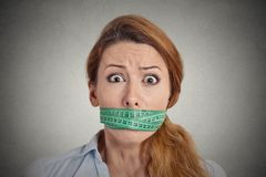 Unhappy young woman with measuring tape covering mouth Royalty Free Stock Images