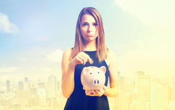Unhappy young woman with pink piggy bank Royalty Free Stock Photos