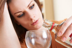 Unhappy Young Woman Pouring Vodka Into Glass Stock Images