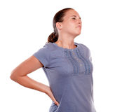 Unhappy young woman with a terrible back pain. Standing over white background Royalty Free Stock Image