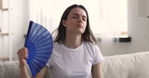 Unhappy young woman waving fan feeling uncomfortable hot at home