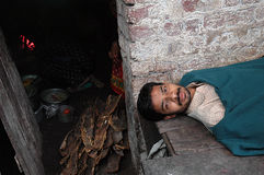 Unhealthy. An Indian Man at slum area of Kolkata is lying down suffering from fever on a small wooden bed just outside his room, where cooking with wooden fired Royalty Free Stock Images