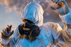 Unhealthy air contaminated by pollution, man with mask and protective suit, concept of biological diseases and environmental prob stock image