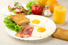 Unhealthy breakfast with bacon, eggs,toasts with salad Royalty Free Stock Image