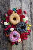 Unhealthy but delicious group of sweet sugar donut cakes and lots of gummy candies on vintage wooden table stock photography
