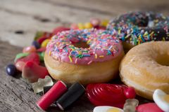 Unhealthy but delicious group of sweet sugar donut cakes and lots of gummy candies on vintage wooden table stock photo
